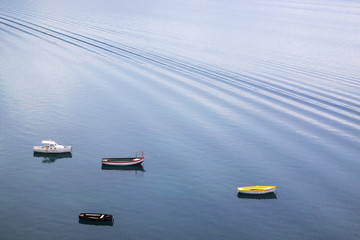 four small wooden boats on the lake