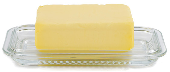 Piece of butter on glass butter dish over white background.
