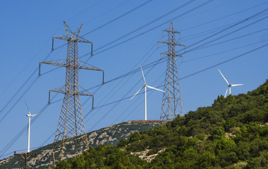 Wind turbines and high voltage electricity towers