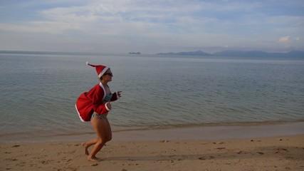Sexy Woman in Santa Hat Running on Sea Beach. Slow Motion.