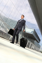 businessman walking with suitcase and trolley