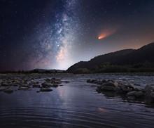Kometa nad rzeką w nocy