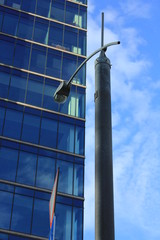 Street lamp near a glass wall of high office building