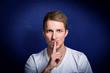 canvas print picture - junger mann mit finger vor dem mund bittet um ruhe