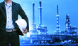 Leinwandbild Motiv engineering man and safety helmet standing against oil refinery