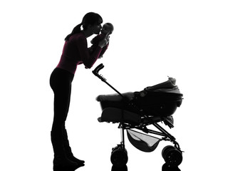 woman prams holding kissing baby silhouette