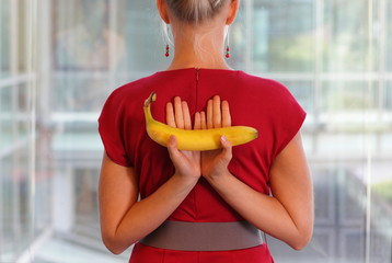 fit business woman with banana as a healhy snack