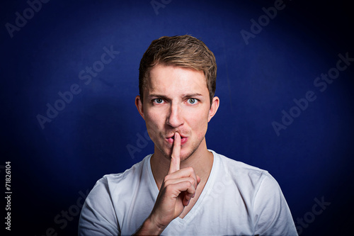 canvas print picture junger mann mit finger vor dem mund bittet um ruhe