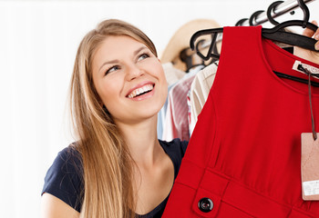 Young lady dreaming of new dress purchase in shopping mall