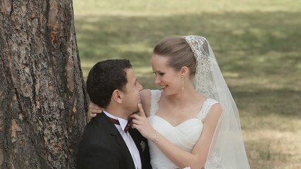 Bride and groom sitting in a park on the grass and laughing