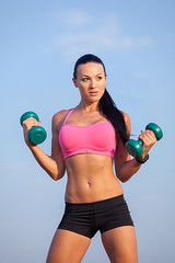 Portrait  woman in fitness wear exercising with dumbbell,