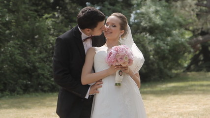 The groom sensually kisses his  young bride in the park
