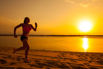 Woman running alone at beautiful sunset in the beach