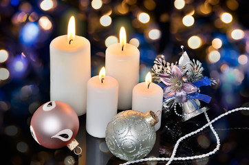 four white lighted candles and Christmas decorations on a bokeh