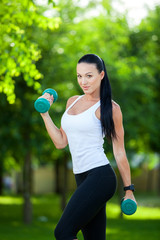 Portrait of cheerful woman in fitness wear exercising with dumbb
