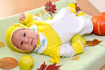The cheerful baby lies among autumn leaves and fruit