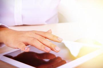 Woman using digital tablet on light background