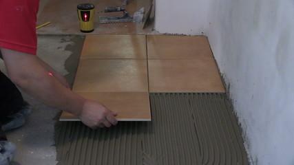 Home improvement, renovation - handyman lay tile on room floor