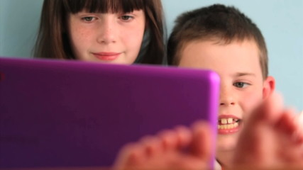 Happy children laughing using laptop