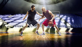 Two basketball players in action in the gym