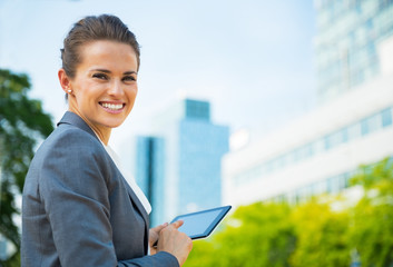 Happy business woman using tablet pc in office district