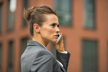 Serious business woman talking cell phone