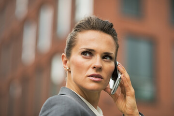 Portrait of serious business woman talking cell phone