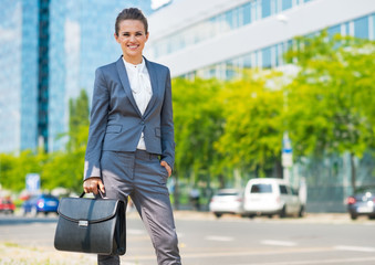 Happy business woman with briefcase in office district