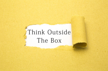 Think outside the box text on torn brown paper