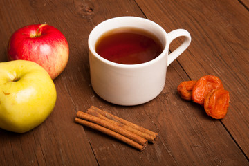 Cup of tea on old wooden table with two apples, dried apricots a