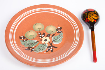 Russian traditional rustic ceramic plate and wooden spoon