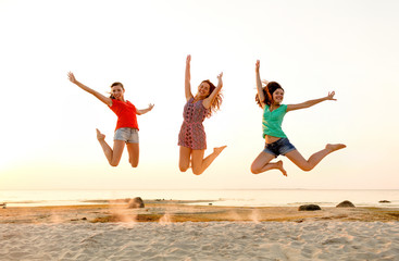 smiling teen girls jumping on beach