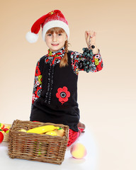 Little girl in santa claus hat holding a bunch of grapes.