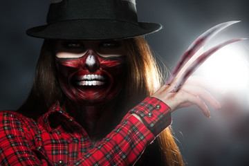 Scary halloween portrait of woman with knifes in hand