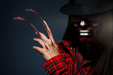 Scary halloween portrait of female with knifes in hand