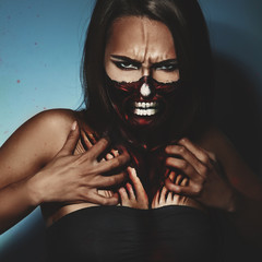 Halloween style photo of woman with fac and body art