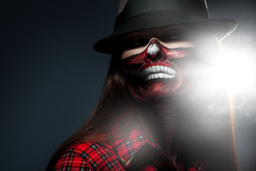 Adult woman with scary face art for halloween night looking at c