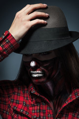 Attractive adult woman with scary halloween style make up lookin