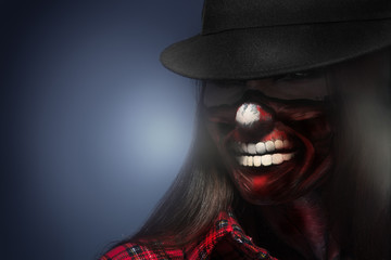 Woman in har with scary face art for halloween night looking awa