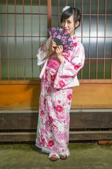 Asian woman in kimono holding fan
