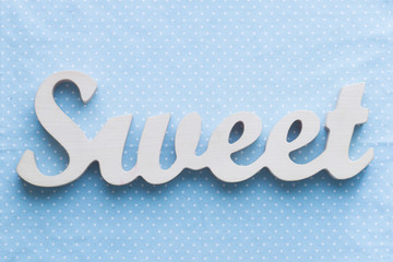 "Wooden word ""sweet"" on a blue polka dots background"