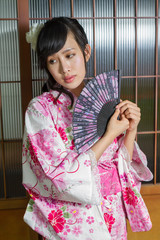 Asian woman in kimono holding fan