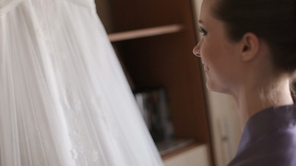 The bride before the wedding, looking at her wedding dress