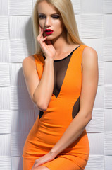 Beautiful blonde woman in orange dress