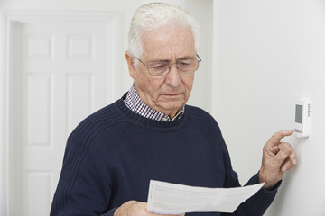 Worried Senior Man With Bill Turning Down Central Heating Thermo