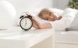 lady has woken up by an alarm clock. eyes open