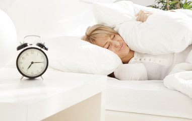 lady has woken up by an alarm clock eyes closed