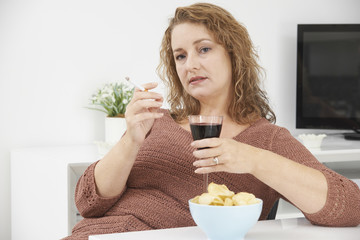 Woman Smoking Cigarette Whilst Drinking Wine And Eating Snacks