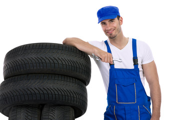 Young mechanic with tires and wrench
