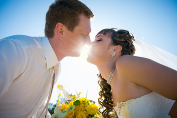 bride and groom kiss through the rays of the sun